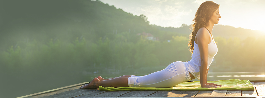 Woman doing yoga on the lake – relaxing in nature